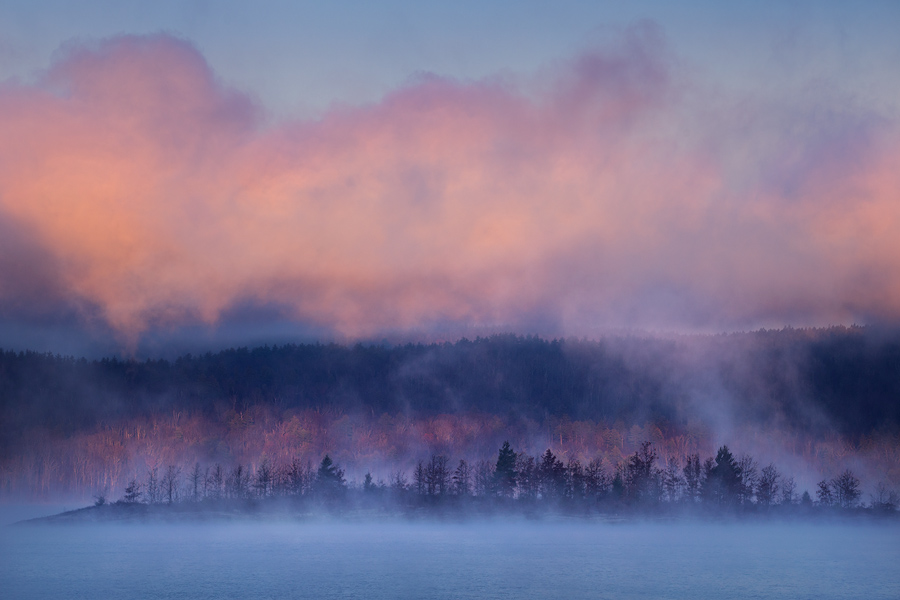On a cold morning in November the morning light catches a blanket of fog lifting off the Quabbin Reservoir casting shadows on...